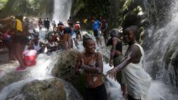 Sejumlah  peziarah mandi di bawah air terjun di Saut d' Eau, Haiti, (16/7). Ini merupakan ritual tahunan untuk menyembuhkan penyakit dan mensucikan diri. (REUTERS/Andres Martinez Casares)