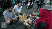 Wisatawan mancanegara membeli sate ayam di Jalan Malioboro, Yogya, Kamis (4/8). Makanan cepat saji ini banyak dijual di sepanjang Jalan Malioboro dengan harga yang terjangkau. (Liputan6.com/Boy Harjanto)