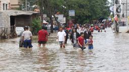 Warga melintasi banjir yang menggenangi Jalan KH Hasyim Ashari, Tangerang, Banten, Kamis (2/1/2020). Banjir yang menggenangi jalan penghubung Jakarta- Tangerang tersebut mulai surut dan sudah bisa dilintasi pejalan kaki. (Liputan6.com/Angga Yuniar)