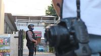 pascabaku tembak polisi dan kelompok MIT di Poso, Personel Polda Sulteng berjaga di pintu masuk RS Bhayangkara Palu pada 16 Mei, 2020. Pemeriksaan ketat dilakukan termasuk terhadap jurnalis yang ingin masuk.