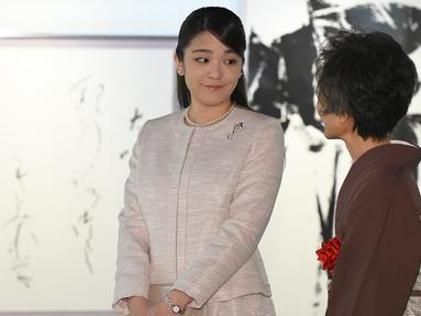 Putri sulung Pangeran Akishino, Putri Mako berbincang saat menghadiri pameran kaligrafi di  Tokyo, Jepang (9/2). Cucu tertua Kaisar Akihito ini menunda pernikahan dengan tunangannya hingga 2020. (AFP Photo/Pool/Toru Yamanaka)