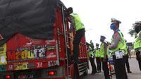 Petugas kepolisian melakukan pengecekan terhadap truk yang keluar Tol Merak, Banten, Senin (18/5/2020). Pemeriksaan (check point) tersebut terkait larangan mudik guna penyekatan atau memeriksa kemungkinan pemudik yang akan keluar dari wilayah Jabodetabek. (Liputan6.com/Angga Yuniar)