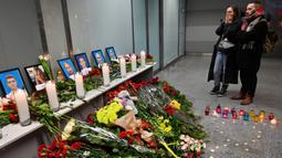Orang-orang memandangi foto para korban pesawat 737-800 Ukraina yang jatuh di Iran, di bandara internasional Borispil, Kiev, Rabu (8/1/2020). Pesawat yang membawa 176 orang itu jatuh setelah lepas landas dari bandara utama Teheran dan menewaskan semua penumpang. (Sergei SUPINSKY/AFP)