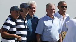 Mantan Presiden AS, Bill Clinton, George W. Bush dan Barack Obama berfoto bersama tim Amerika pada pembukaan pertandingan golf President Cup di New Jersey, Kamis (28/9). Pertama kalinya tiga presiden datang bersama di turnamen ini. (Rob Carr/AFP)