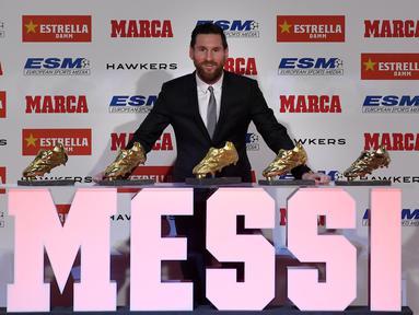 Striker Barcelona, Lionel Messi, berpose di depan trofi Sepatu Emas Eropa di Antiga Fabrica Estrella Damm, Barcelona, Selasa, (18/12/2018). Messi berhak atas penghargaan itu berkat koleksi 34 gol dari 36 pertandingan. (AFP/Lluis Gene)