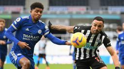 Bek Leicester City, Wesley Fofana (kiri) berebut bola dengan striker Newcastle United, Callum Wilson dalam laga lanjutan Liga Inggris 2020/21 pekan ke-17 di St James' Park, Minggu (3/1/2021). Leicester City menang 2-1 atas Newcastle United. (AFP/Michael Regan/Pool)