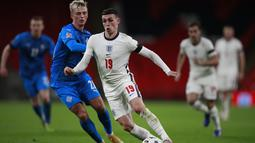 Gelandang Inggris, Phil Foden menggiring bola dari kawalan pemain Islandia, Albert Gudmundsson pada pertandingan UEFA Nations League di stadion Wembley, London (18/11/2020). Meski menang, Inggris tetap gagal lolos ke putaran final atau babak semifinal UEFA Nations League. (AP Photo/Ian Walton, Pool)