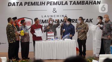 Ketua KPU Arief Budiman (tengah) bersama Wakil Ketua KPU Pramono Ubaid Tanthowi dan Anggota Bawaslu RI Mochammad Afifuddin saat memperlihatkan alat prosedur kesehatan dalam Launching Pemilihan Serentak Tahun 2020 di Gedung KPU RI, Menteng, Jakarta Pusat, Kamis (18/6/2020). (Liputan6.com/Johan Tallo)