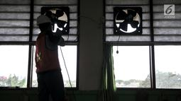 Siswa SMK Negeri 4 Jakarta Utara memasang kipas angin dan penyaring udara di SD Negeri Cilincing 07 Pagi, Jakarta, Kamis (19/9/2019). Instalasi dibuat sebagai kepedulian terhadap siswa SD setempat yang terdampak polusi asap pabrik pembuatan arang serta peleburan aluminium. (merdeka.com/IqbalNugroho)