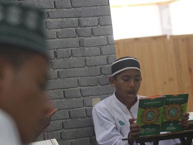 Seorang santri membaca Al-Quran di Pesantren Nuu Waar Al Fatih Kaffah Nusantara (AFKN) di Setu, Kabupaten Bekasi, Jawa Barat, Sabtu (1/5/2021). Kegiatan Khatam Al-Quran tersebut dilakukan rutin setiap bulan Ramadhan oleh 750 santri dan santriwati. (Liputan6.com/Herman Zakharia)