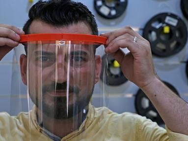 Seorang anggota staf mengenakan pelindung wajah cetak 3D yang dibuat di bawah proyek Glia, yang menghasilkan pasokan medis murah untuk daerah miskin, selama pandemi COVID-19 yang sedang berlangsung di Kota Gaza (13/7/2020). (AFP/Mohammed Abed)