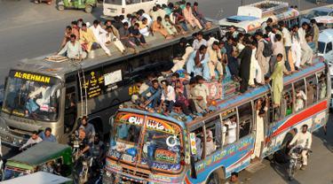 Sejumlah penumpang duduk di atas atap bus saat mudik menuju kampung halaman untuk merayakan Idul Adha di Lahore, Pakistan, Sabtu (10/8/2019). Umat Islam di seluruh dunia merayakan Idul Adha yang identik dengan tradisi berkurban. (Photo by ARIF ALI / AFP)