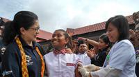 Menteri Kesehatan Republik Indonesia, Nila Moeloek Bersama Siswi SD di Papua Barat Saat Melakukan Imunisasi MR
