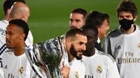 Striker Real Madrid, Karim Benzema, mengangkat trofi juara La Liga usai mengalahkan Villrreal pada laga lanjutan pekan ke-37 di Estadio Alfredo Di Stefano, Jumat (17/7/2020) dini hari WIB. Real Madrid menang 2-1 atas Villarreal. (AFP/Gabriel Bouys)