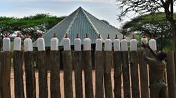 Naomi, salah seorang penjaga menata sejumlah botol berisi susu formula untuk anak-anak gajah di Reteti Elephant Sanctuary, Namunyak Wildlife Conservancy, Kenya, Rabu (26/2/2020). Anak-anak gajah di sini dirawat hingga siap untuk dilepaskan kembali ke alam liar. (TONY KARUMBA/AFP)