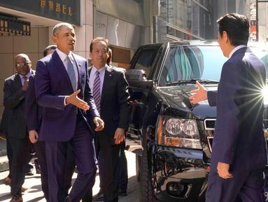 PM Jepang, Shinzo Abe menyambut Presiden AS ke-44 Barack Obama saat tiba di salah satu restoran sushi di kawasan Ginza, Tokyo, Jepang, (25/3). Obama dan Abe makan siang bersama di restoran tersebut. (AP Photo / Shizuo Kambayashi, Pool)