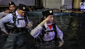 Artis peran Marsha Aruan masuk ke air untuk melakukan pengibaran bendera di dalam akuarium Seaworld Ancol, Jakarta, Jumat (17/8). Marsha terpilih sebagai salah satu pengibar bendera di dalam air memperingati HUT ke-73 RI. (Liputan6.com/Faizal Fanani)