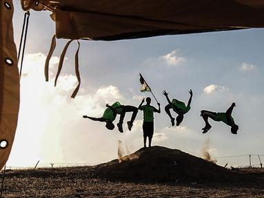 Empat pemuda Palestina mempraktekkan keterampilan parkour mereka di dekat tenda warga di perbatasan Gaza, Palestina (10/4). Mereka menghibur para warga yang melakukan aksi protes di perbatasan Gaza tersebut. (AFP Photo/Said Khatib)