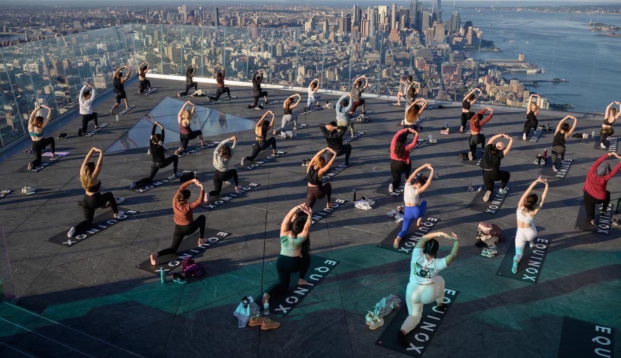 Praktisi yoga menghadiri kelas di Edge Observation Deck, Manhattan, New York, Amerika Serikat, Kamis (17/6/2021). Edge Observation Deck disebut sebagai 'dek langit luar ruang tertinggi di Belahan Barat'. (Ed JONES/AFP)