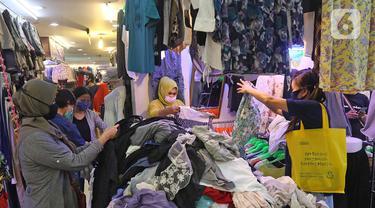 Calon pembeli memilih pakaian bekas di salah satu kios Pasar Senen Blok III, Jakarta, Kamis (11/6/2020). Pasar yang tetap buka saat PSBB dengan pembatasan jam operasional ini akan kembali dibuka secara normal pada 15 Juni 2020 dengan aturan protokol kesehatan COVID-19. (Liputan6.com/Herman Zakharia)