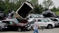 Seorang pekerja berjalan melewati deretan mobil yang rusak akibat tornado di sebuah dealer di Jefferson City, Missouri, AS, Kamis (23/5/2019). Tiga orang tewas akibat tornado yang menyapu Missouri sehari sebelumnya. (AP Photo/Charlie Riedel)