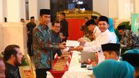 Presiden Joko Widodo (kiri) menerima bukti setor pembayaran zakat seusai membayar zakat mal kepada Badan Amil Zakat Nasional (Baznas) di Istana Negara, Jakarta, Kamis (16/5/2019). Jokowi menyerahkan zakat penghasilan senilai Rp 55 juta secara tunai. (Liputan6.com/Angga Yuniar)