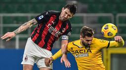 Bek AC Milan, Alessio Romagnoli (kiri) berduel udara dengan striker Udinese, Fernando Llorente dalam laga lanjutan Liga Italia 2020/21 pekan ke-25 di San Siro Stadium, Rabu (3/3/2021). AC Milan bermain imbang 1-1 dengan Udinese. (AFP/Miguel Medina)