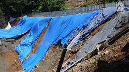 Pekerja melintasi area lokasi longsor di kawasan Ciloto, Cianjur, Jawa Barat, Sabtu (31/3). Longsor yang terjadi pada Rabu (28/3) lalu diduga adanya pergerakan tanah sehingga menyebabkan longsor. (Liputan6.com/Helmi Fithriansyah)
