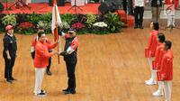 Ketua KOI, Erick Thohir (kedua kiri) menyerahkan bendera Merah Putih kepada Ketua Kontingen Indonesia untuk Asian Games 2018, Komjen Pol Syafruddin saat upacara pengukuhan di Istora Senayan, Jakarta, Minggu (5/8). (Liputan6.com/Helmi Fithriansyah)