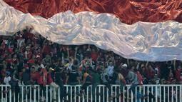 Suporter Timnas Indonesia mengibarkan bendera raksasa saat melawan Thailand pada laga Final Piala AFF 2016 di Stadion Pakansari, Bogor, (14/12/2016). (Bola.com/Nicklas Hanoatubun)