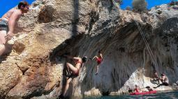 Peserta berpartisipasi dalam Festival Mendaki tahunan 2019 di pulau Kalymnos, Yunani (4/10/2019). Pemandangan menakjubkan dan cuaca bagus menjadikan pulau ini sebagai tujuan utama bagi pemanjat tebing internasional dari semua tingkatan dengan lebih dari 2500 rute pendakian. (AFP Photo/Aris Messinis)