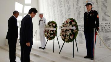 Presiden AS, Barack Obama dan PM Jepang, Shinzo Abe menundukan kepala saat upacara peletakan karangan bunga di atas kapal USS Arizona Memorial Perang Dunia II di Joint Base Pearl Harbor-Hickam, Hawaii, (27/12). (REUTERS/Kevin Lamarque)