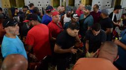 Sejumlah peserta membawa ayam mereka untuk bertanding di klub sabung ayam Campanillas, Toa Baja, Puerto Rico, Rabu (18/12/2019). Puerto Rico menentang undang-undang federal yang akan menutup sabung ayam legal di teritorial Amerika Serikat mulai minggu ini. (AP Photo/Carlos Giusti)