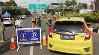 Petugas gabungan mengarahkan kendaraan saat penerapan ganjil genap di Jalan Raya Puncak, Gadog, Kabupaten Bogor, Jawa Barat, Jumat (3/9/2021). Jika uji coba tersebut efektif mengurai kepadatan akan dilanjutkan terus setiap akhir pekan. (Liputan6.com/Herman Zakharia)