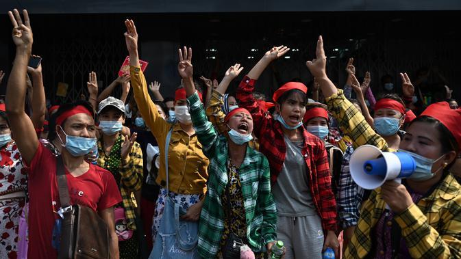 Para pengunjuk rasa mengacungkan salam tiga jari saat demonstrasi menentang kudeta militer di Yangon, Myanmar pada Sabtu (6/2/2021). Penangkapan Suu Kyi dan para pemimpin senior lainnya minggu ini menghentikan pemerintahan demokrasi selama 10 tahun terakhir. (YE AUNG THU / AFP)