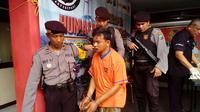 Sholeh, 23 tahun, tersangka pembunuhan saat tiba di Mapolres Bangkalan. (liputan6.com/Musthofa Aldo)