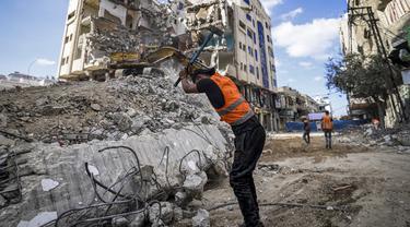 Seorang pekerja Palestina memecahkan puing-puing dari sebuah bangunan yang hancur selama konflik Mei 2021 antara Hamas dan Israel di Kota Gaza, Sabtu (5/6/2021). (MAHMUD HAMS/AFP)