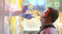 Seorang calon penumpang melakukan tes cepat atau rapid test antigen gratis di Terminal Kalideres, Jakarta Barat, Rabu (21/01/2021). Rapid test antigen gratis bagi calon penumpang dan kru bus tersebut berlangsung hingga 25 Januari mendatang. (merdeka.com/Arie Basuki)