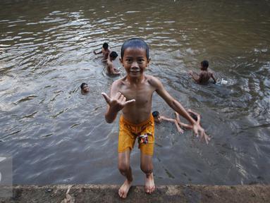 Sejumlah anak mandi di Sungai Ciliwung, Jakarta, Rabu (16/11). Cuaca panas di Jakarta membuat anak-anak tersebut mandi di sungai untuk mendinginkan suhu tubuh. (Liputan6.com/Gempur M Surya)