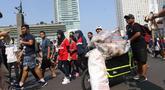 Sejumlah relawan melakukan gerakan bersih sampah plastik di kawasan Car Free Day, Bundaran HI, Jakarta, Minggu (21/10). Gerakan tersebut untuk meningkatkan kesadaran masyarakat mengenai ancaman sampah plastik bagi Bumi. (Liputan6.com/Angga Yuniar)