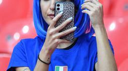 Fans wanita Italia melihat ponsel sambil merapikan rambutnya sebelum pertandingan semifinal EURO 2020 antara Italia dan Spanyol di Stadion Wembley di London (7/7/2021). (AFP/Pool/Justin Tallis)