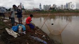 Beberapa warga tengah mencari ikan dengan menggunakan jala di Banjir Kanal Barat, Tanah abang, Jakarta, Sabtu (4/1/2020). Debit air yang mulai surut di aliran tersebut dimanfaatkan warga untuk mencari ikan. (Liputan6.com/Angga Yuniar)