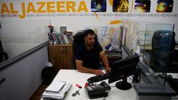 Seorang karyawan berada di balik mejanya di kantor berita Al Jazeera, Yerusalem, 31 Juli 2017. Israel menuduh Al Jazeera mendukung terorisme, dan menyebutkan bahwa saluran bahasa Arab dan bahasa Inggrisnya akan diblokir. (AHMAD GHARABLI/AFP)