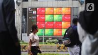 Pejalan kaki melintas dekat layar pergerakan Indeks Harga Saham Gabungan (IHSG) di kawasan Jakarta, Senin (13/1/2020). IHSG sore ini ditutup di zona hijau pada level 6.296 naik 21,62 poin atau 0,34 persen. (Liputan6.com/Angga Yuniar)