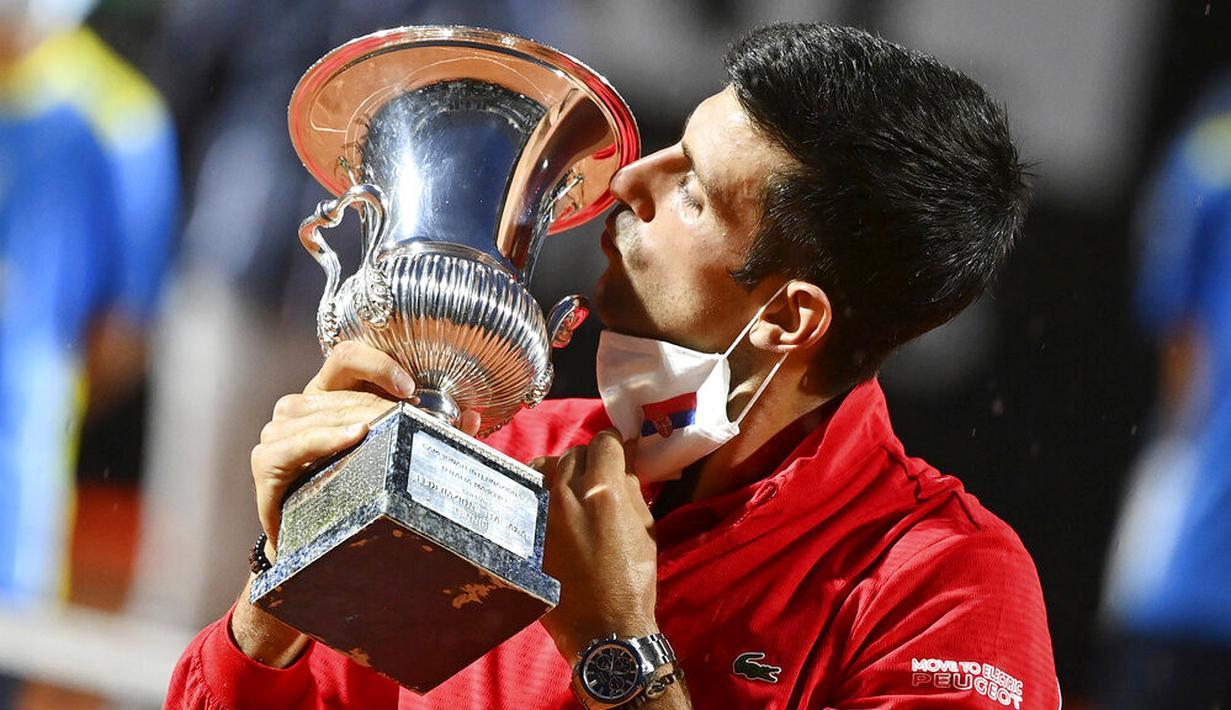 Petenis Serbia, Novak Djokovic, mencium trofi usai menjuarai Italia Terbuka di Roma, Senin (21/9/2020). Djokovic mengalahkan petenis Argentina, Diego Schwartzman, dengan skor 7-5 dan 6-3. (Alfredo Falcone/LaPresse via AP)