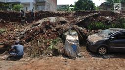 Pekerja membenahi material tembok perumahan Lereng Indah yang longsor dan menimpa kendaraan di Perumahan Lereng Bukit Indah, Pondok Cabe Udik, Pamulang,Tangerang Selatan, Senin (8/4). Dua mobil warga perumahan Lereng Indah rusak tertimpa longsor saat hujan deras. (merdeka.com/Arie Basuki)