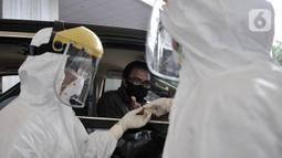 Tim medis mengambil sampel darah salah satu pengemudi saat Rapid Test Drive Thru di Kemenhub, Jakarta, Senin (20/4/2020). Kemenhub menggelar Rapid Test Drive Thru kepada pengemudi angkutan umum seperti taksi dan ojek online guna mencegah penyebaran virus Covid-19. (merdeka.com/Iqbal S. Nugroho)
