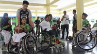 Timnas basket kursi roda Indonesia bersama anak-anak berkebutuhan khusus di Yayasan Pembinaan Anak Cacat (YPAC) Surakarta, Rabu (19/9/2018). (Bola.com/Ronald Seger)