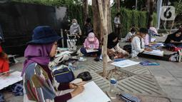 Sejumlah mahasiswa Institut Kesenian Jakarta melukis suasana di sekitar kawasan Bundaran HI Jakarta, Kamis (5/12/2019). Kegiatan melukis ini merupakan salah satu tugas bagi mahasiswa baru guna mengembangkan keahlian dalam bidang seni rupa. (Liputan6.com/Faizal Fanani)