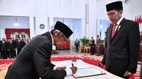Artidjo Alkostar (kiri) menandatangani nota pelantikan sebagai Dewan Pengawas KPK disaksikan Presiden Joko Widodo di Istana Negara, Jakarta, Jumat (20/12/2019). Upacara pelantikan Dewan Pengawas KPK dipimpin langsung Presiden Joko Widodo. (Foto: Biro Pers Setpres)